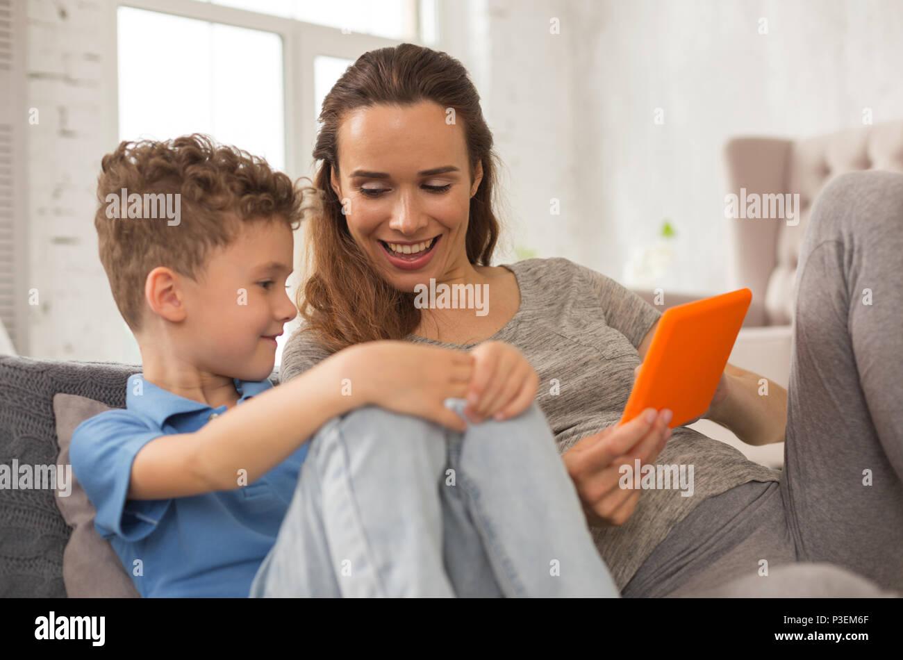 Ridendo madre sorridente largamente mentre raccontano barzellette Immagini Stock