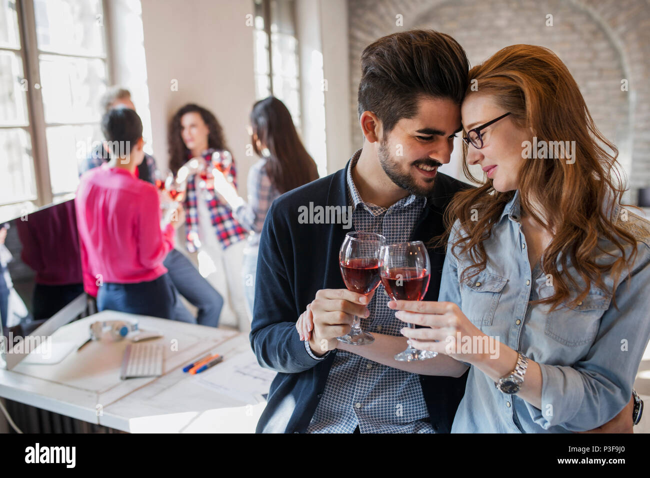 Felice giovani architetti avente pausa e bere il vino Immagini Stock