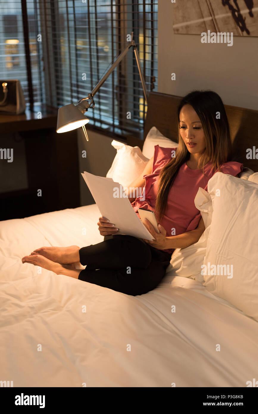 Imprenditrice seduta sul letto la lettura dei documenti Immagini Stock