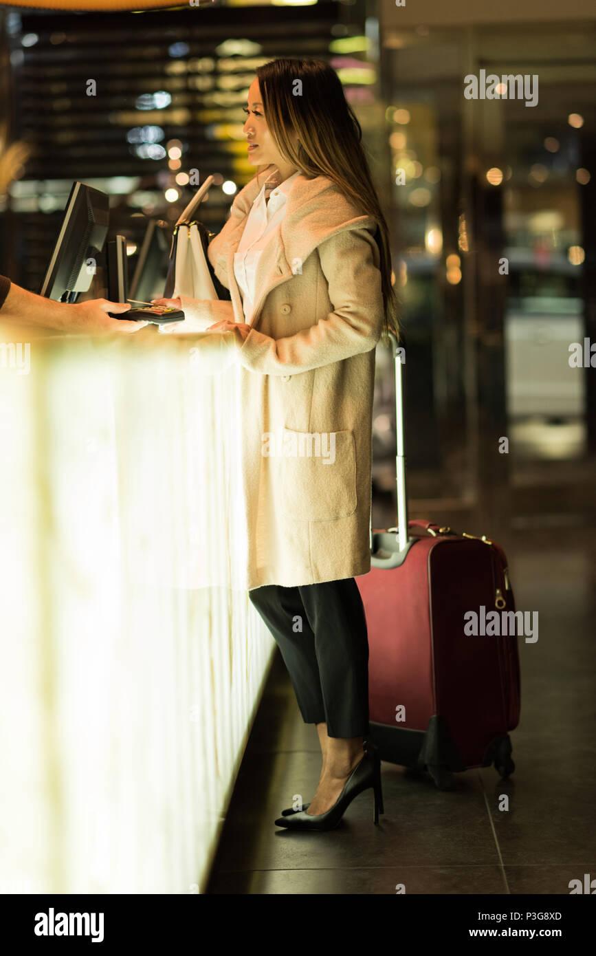 Imprenditrice in piedi presso la reception wit il suo bagaglio Immagini Stock