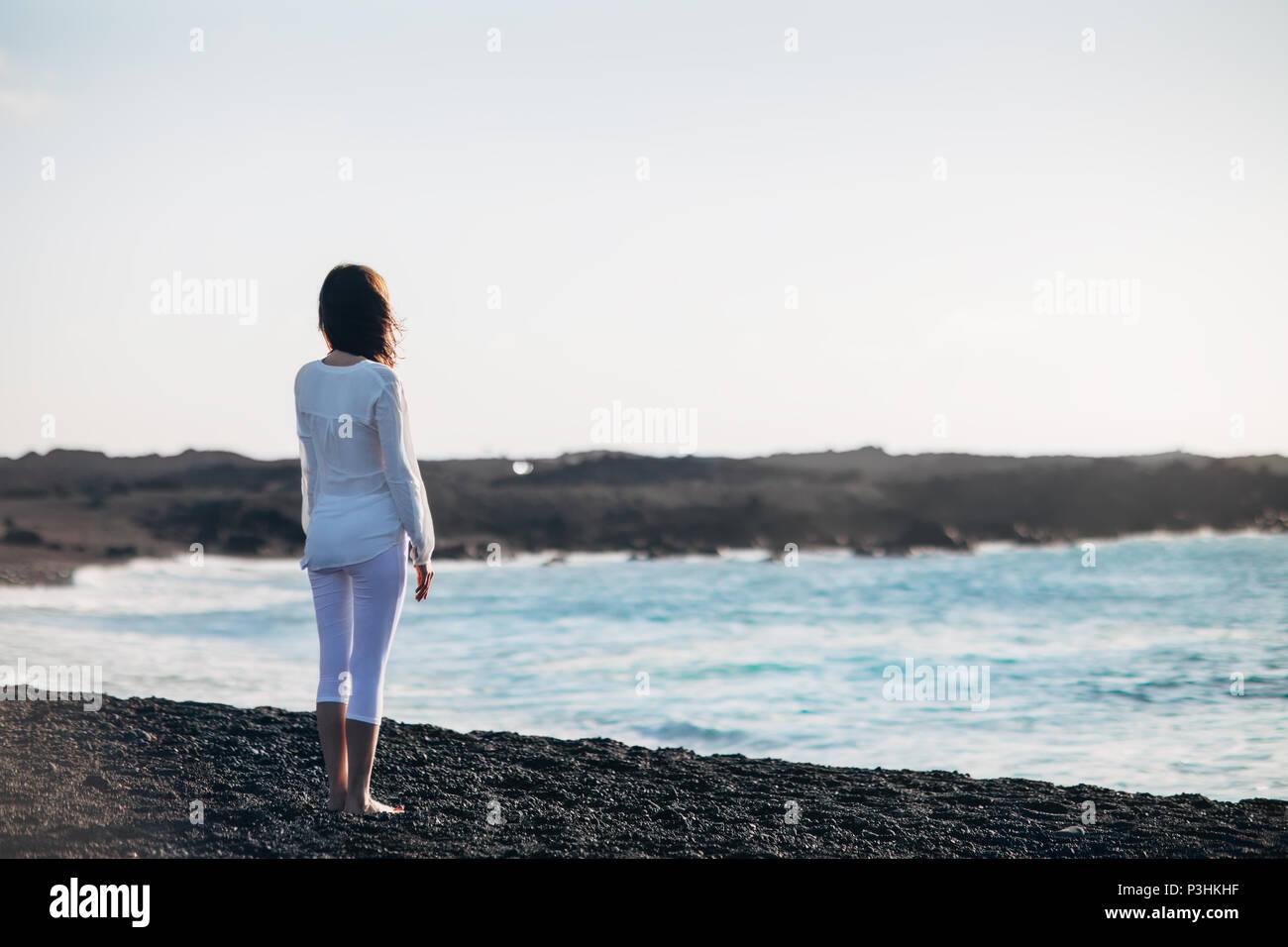 Vista posteriore della giovane donna solitaria godendo di mare sulla spiaggia di sabbia nera. Isole Canarie, Spagna. Concetto di solitudine Immagini Stock