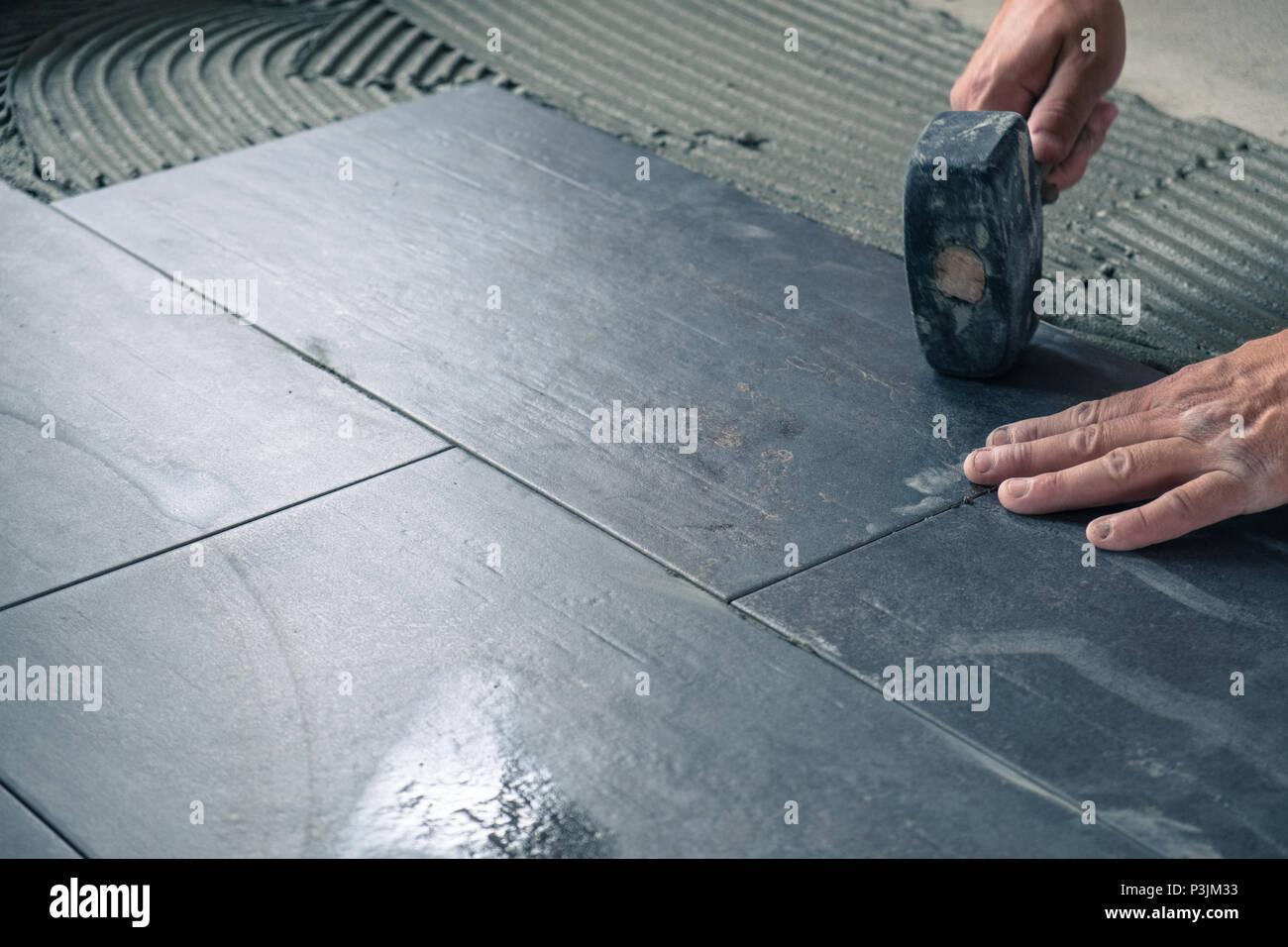 Lavoratore immissione piastrelle da pavimento sulla superficie