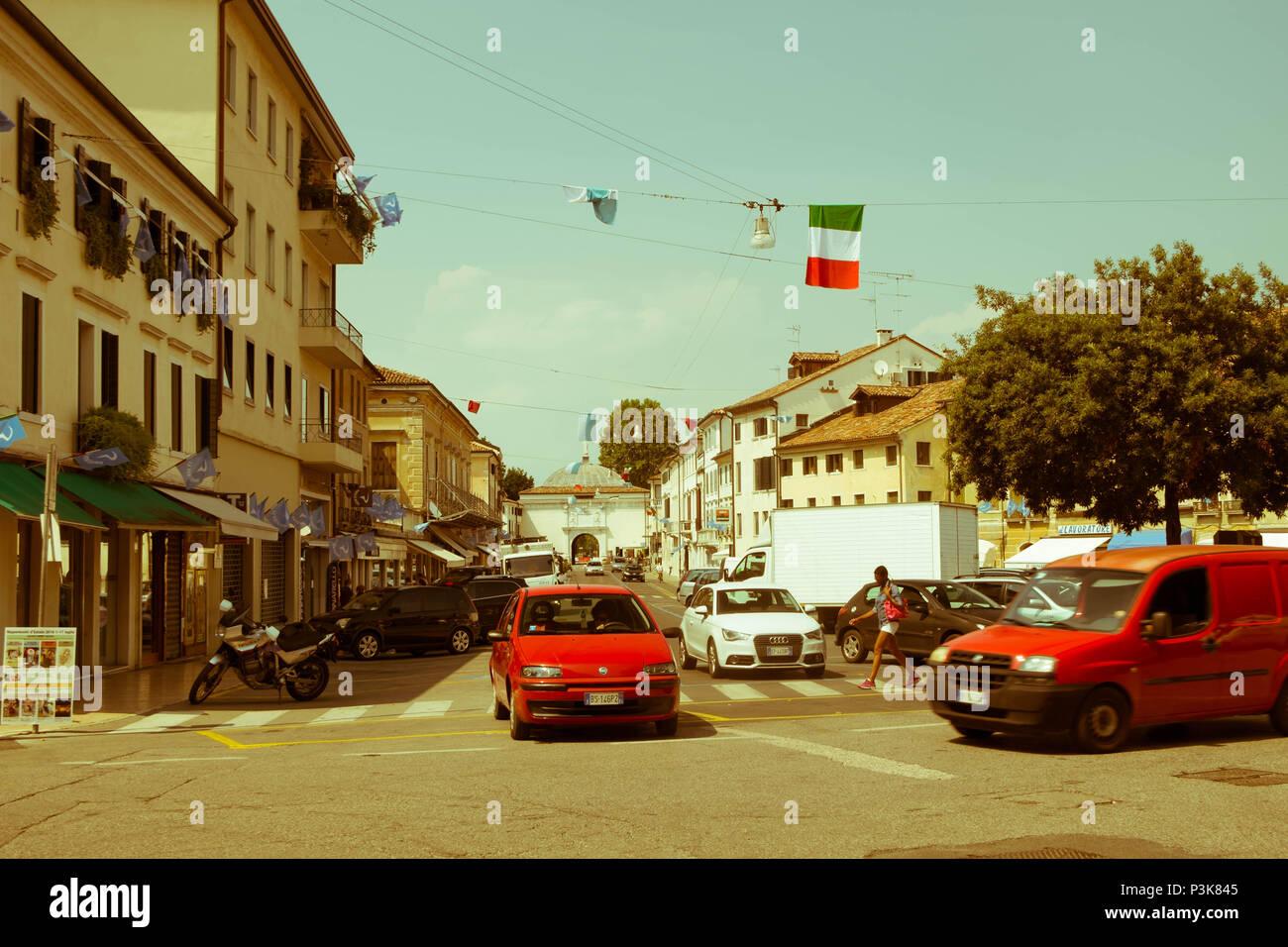 Una vettura attende per un'altra auto per passare a un incrocio. Un pedone cammina sulle strisce pedonali. Questa è la vita quotidiana nella città di Treviso. Immagini Stock