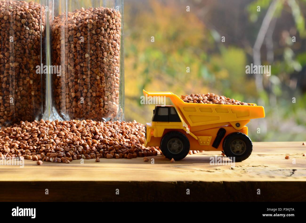 Un piccolo giocattolo giallo carrello è caricato marrone con i chicchi di grano saraceno intorno al mucchio di grano saraceno e un bicchiere della groppa. Una macchina su di una superficie di legno contro un Immagini Stock