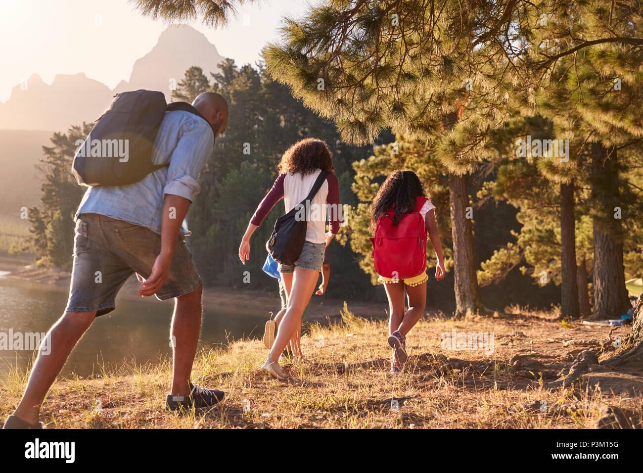I bambini a piedi dal lago con i genitori sulla famiglia escursioni avventura Immagini Stock