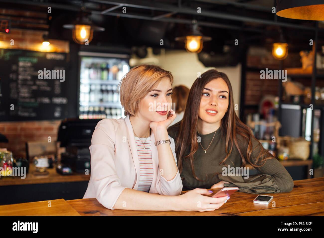 Due bella ragazza chat amici sullo smartphone al cafe Immagini Stock