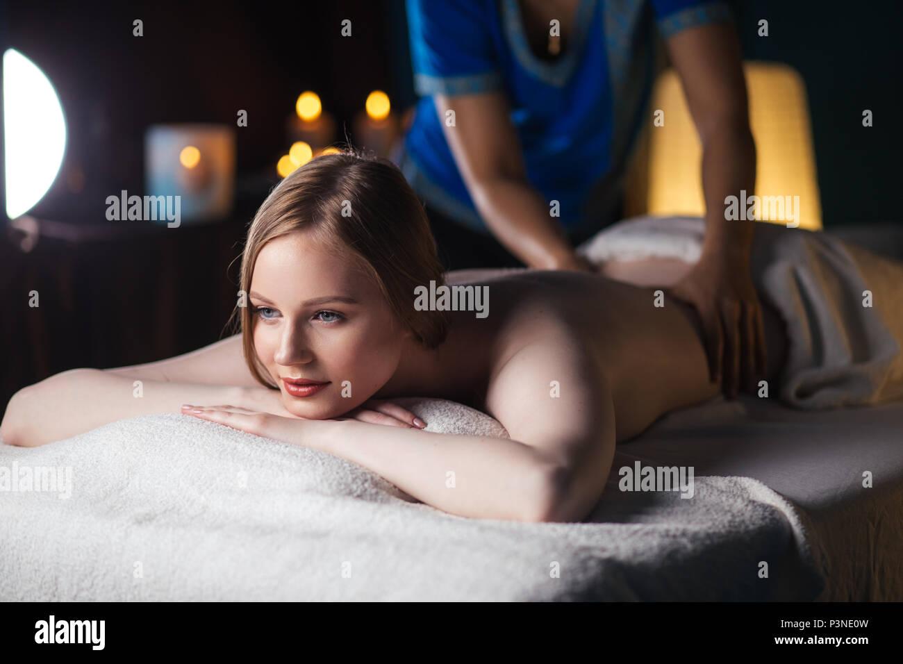 Mani massaggio del dorso, giacente sul ventre di una donna Immagini Stock