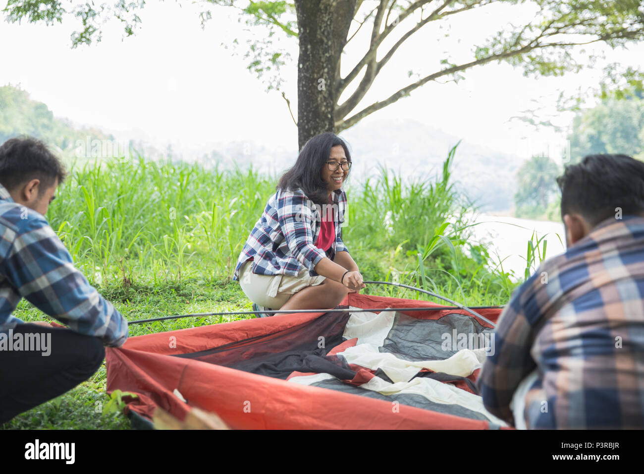 Amici escursionista imposta la tenda Immagini Stock