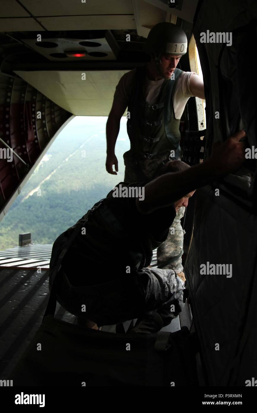Uno studente (in alto) e istruttore (fondo) dell'U.S. Esercito il Comando Operazioni Speciali linea statica jumpmaster corso guarda per punti di riferimento dalla porta di una casa 212 aeromobili durante l'evento culminante del corso, 27 luglio. Del 40 paracadutisti che hanno iniziato il corso, LED da 4 informazioni militari Support Group jumpmasters, solo 23 completato con successo. Il corso si concentra sulle azioni intraprese sul terreno e nell'aria di uscita in modo sicuro i paracadutisti da un certo numero di diversi aerei. (U.S. Foto dell'esercito da Staff Sgt. Kissta DiGregorio/rilasciato) Immagini Stock