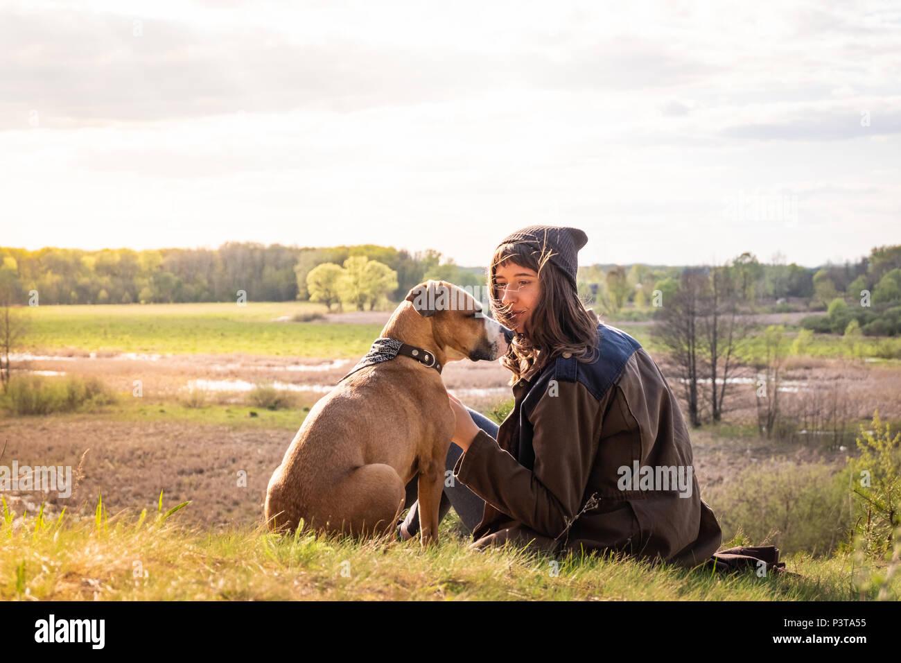 Bellissime escursioni ragazza sedersi sulla collina con il cane a camminare. Giovani femmine persona insieme a staffordshire terrier a prato su caldo pomeriggio soleggiato Immagini Stock