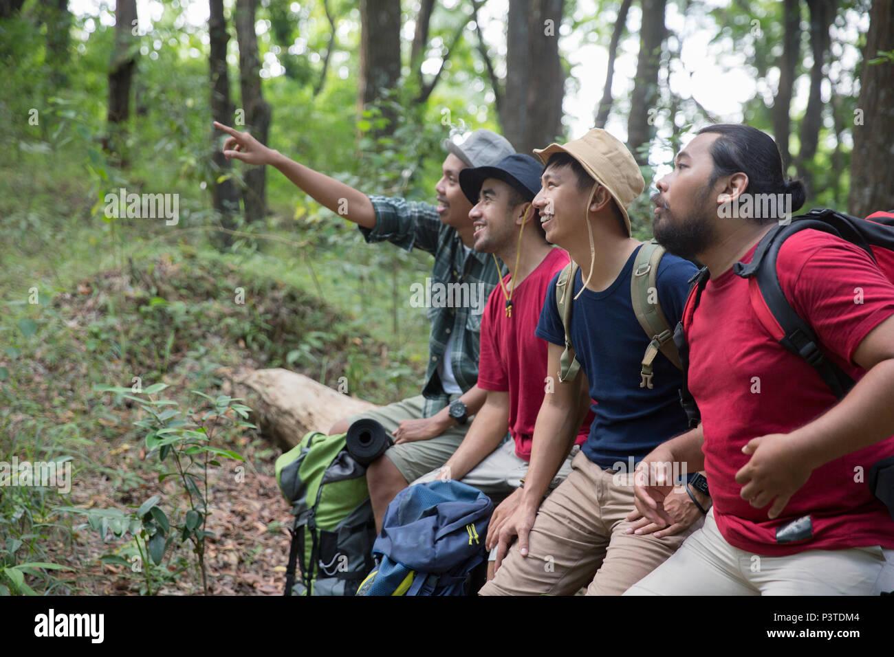 Asian escursionista seduto e puntamento Immagini Stock