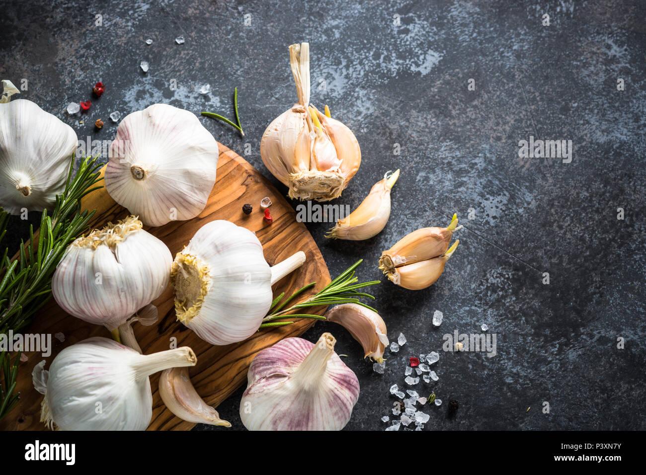 Spicchi di aglio con le spezie e le erbe su una pietra scura sullo sfondo. Vista superiore, copia dello spazio. Immagini Stock