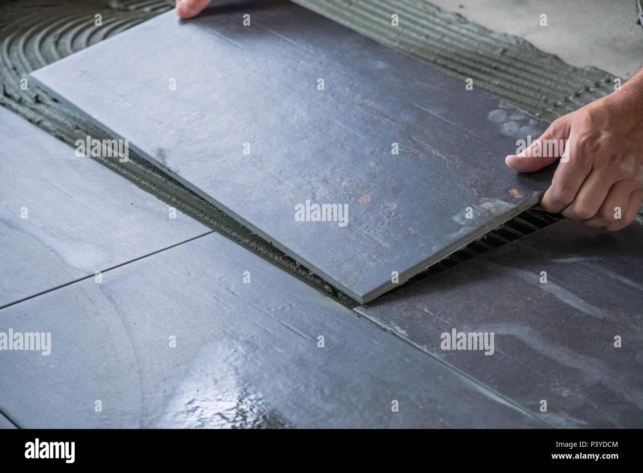 Del lavoratore ponendo le mani ceramica per pavimenti di