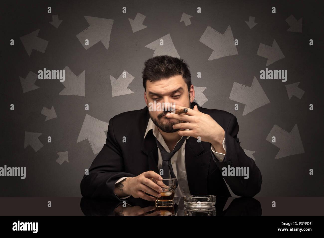 Ubriaco deluso uomo seduto a tavola con le frecce intorno Immagini Stock