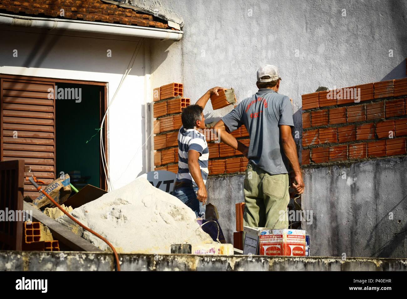 Pedreiros em construção levantando parede de tijolos. Foto Stock