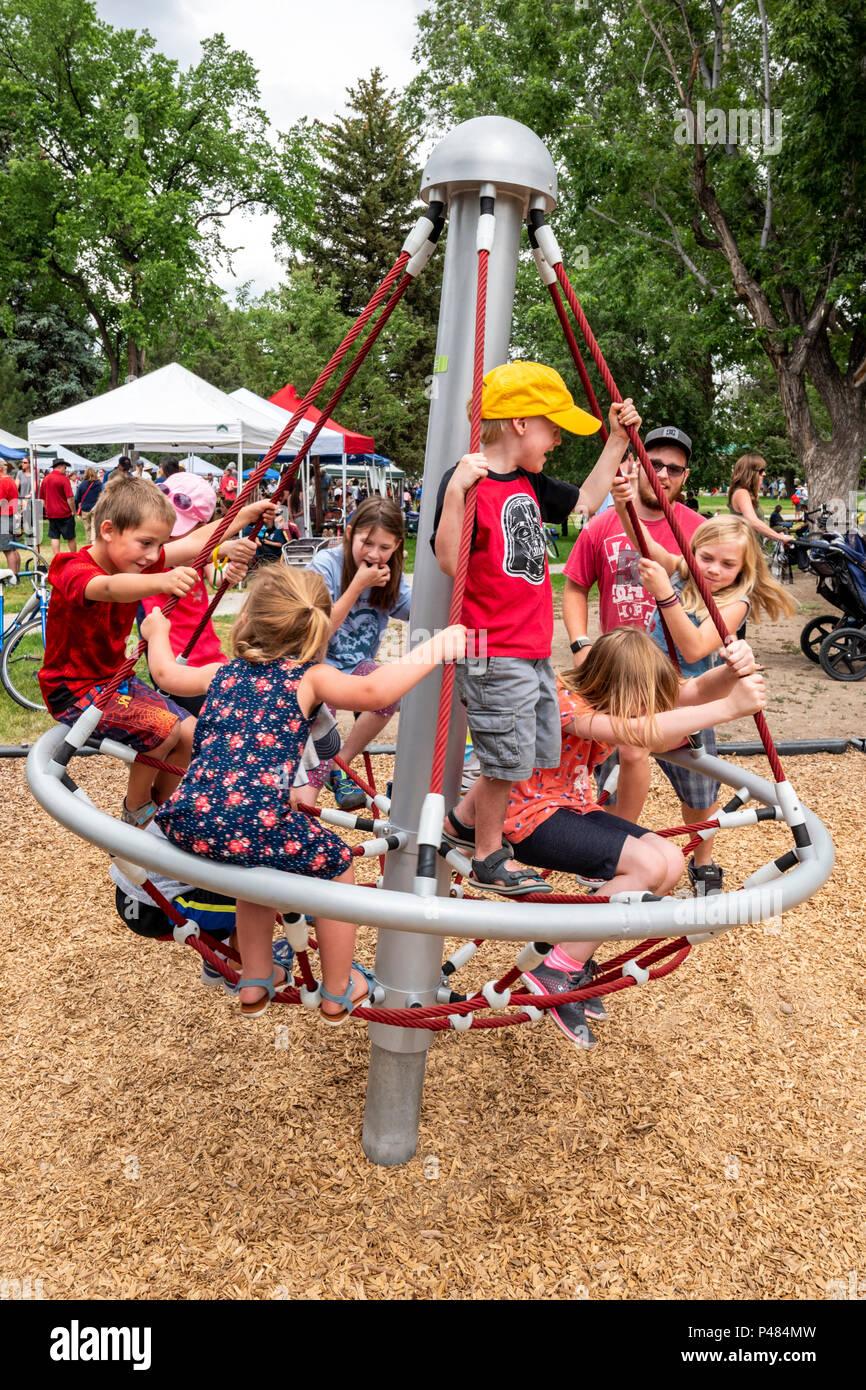 I bambini la filatura sul parco giochi merry-go-round; Salida; Colorado; USA Immagini Stock
