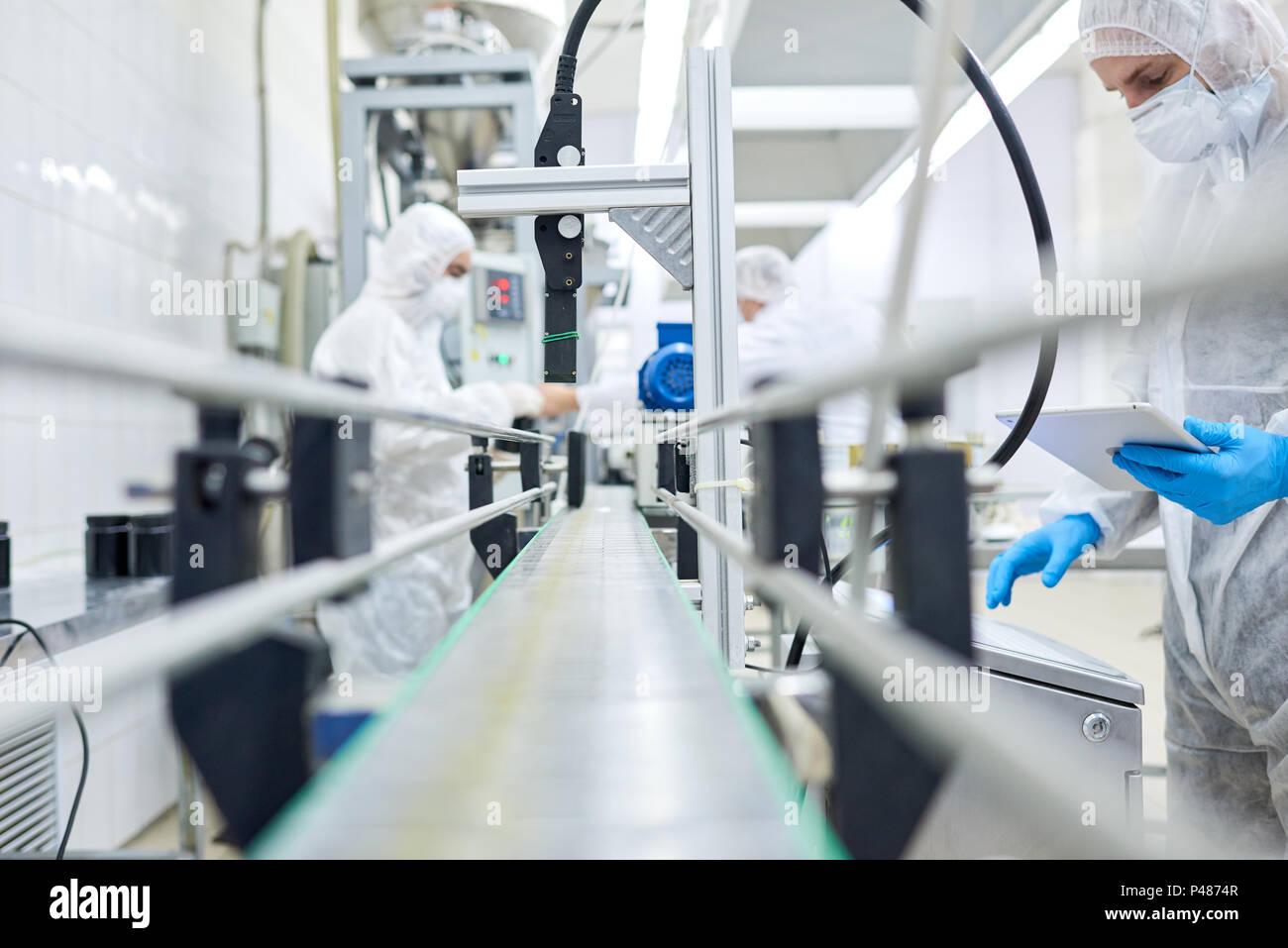 Lavoratori in fabbrica permanente al nastro trasportatore Immagini Stock