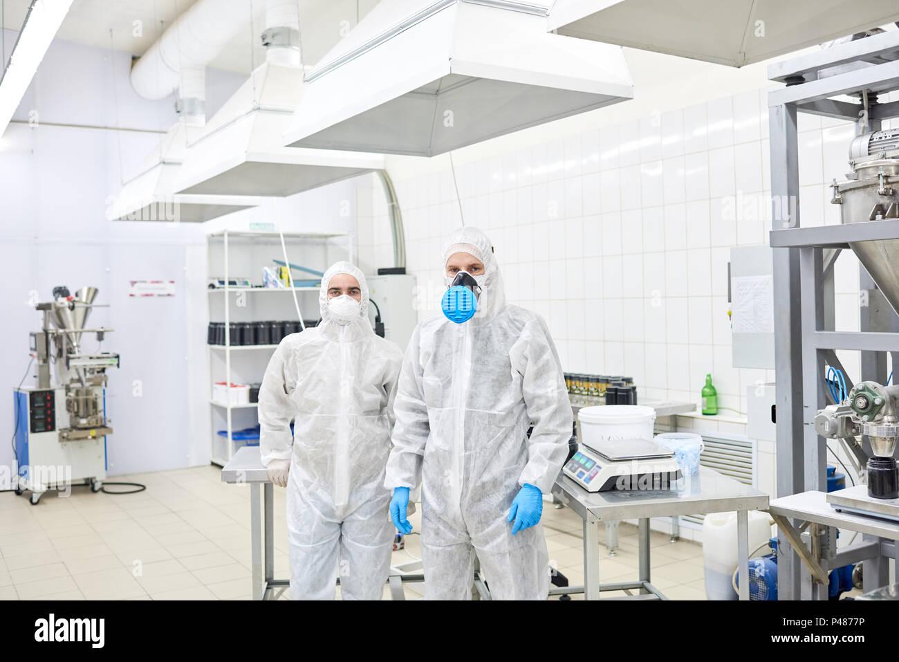I dipendenti di fabbrica in piedi in abbigliamento protettivo Immagini Stock