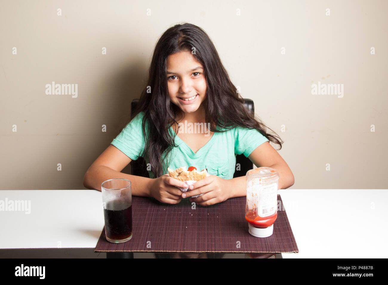 Adolescente comendo hamburguer. São Paulo/SP, Brasile. 030/03/2015. Foto: Irene Araujo / Fotoarena. Immagini Stock
