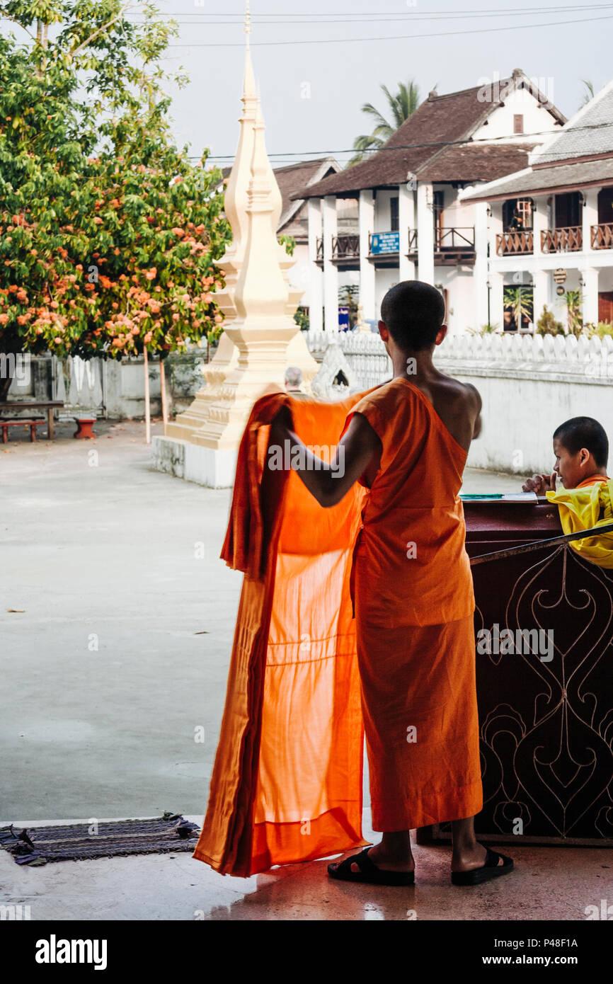 Luang Prabang o Louangphabang, Laos, sud-est asiatico : un laotiano monaco buddista si sparge fuori le vesti guardando verso alcuni stupa dall'Unesco H Immagini Stock