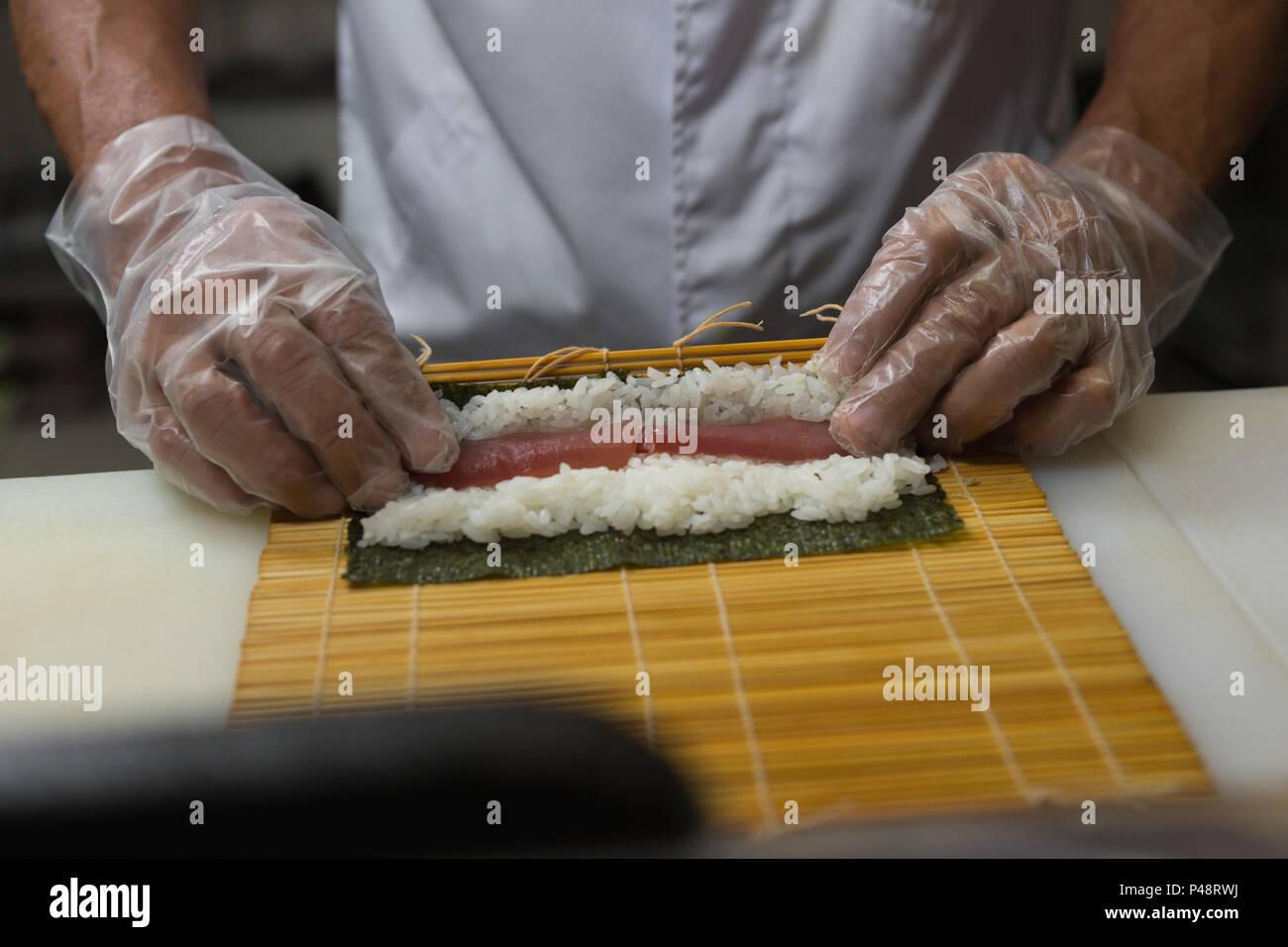 Senior chef prepara sushi in cucina Immagini Stock