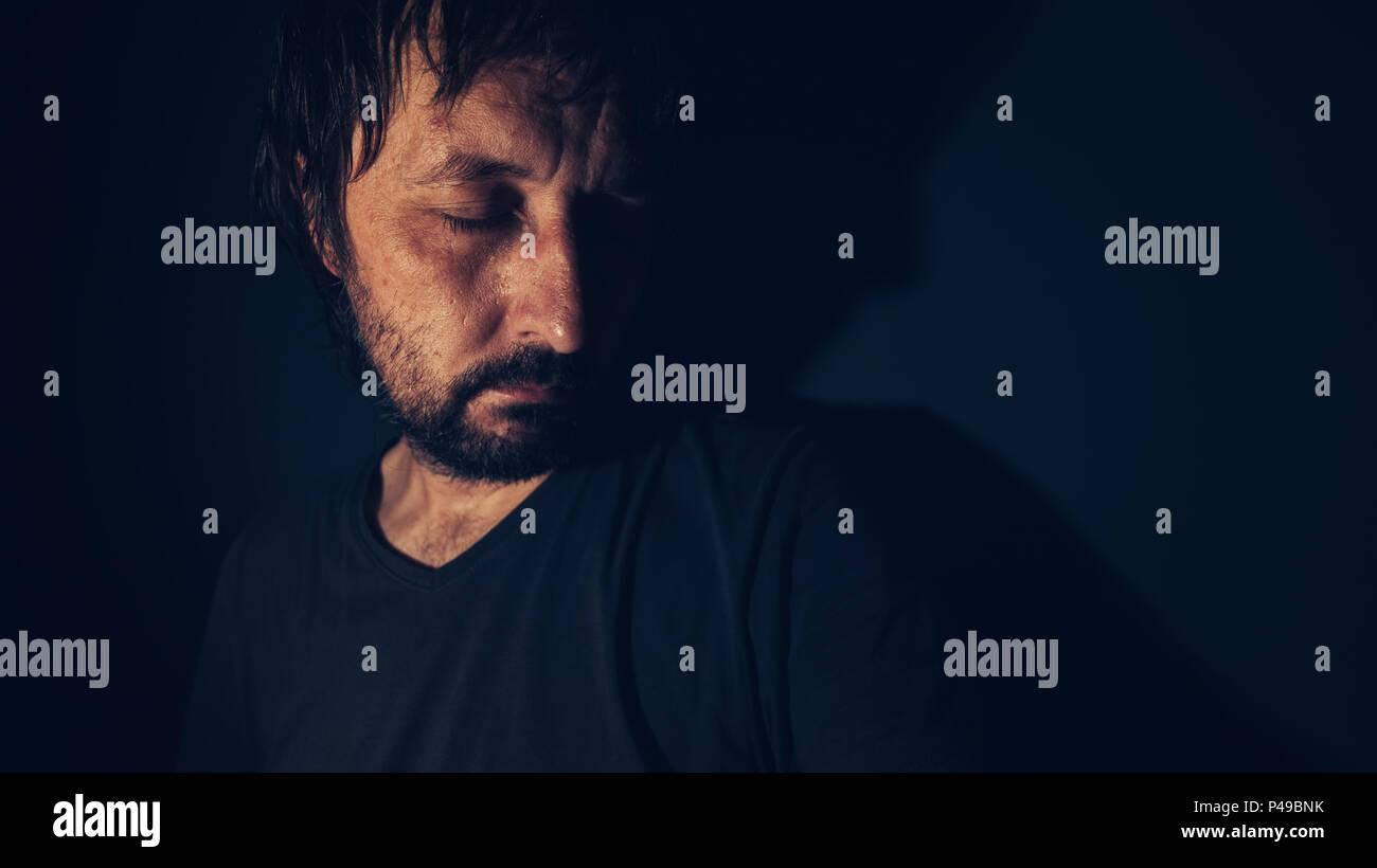 La salute mentale e la depressione concetto, triste depresso broncio uomo nel buio interiore Immagini Stock