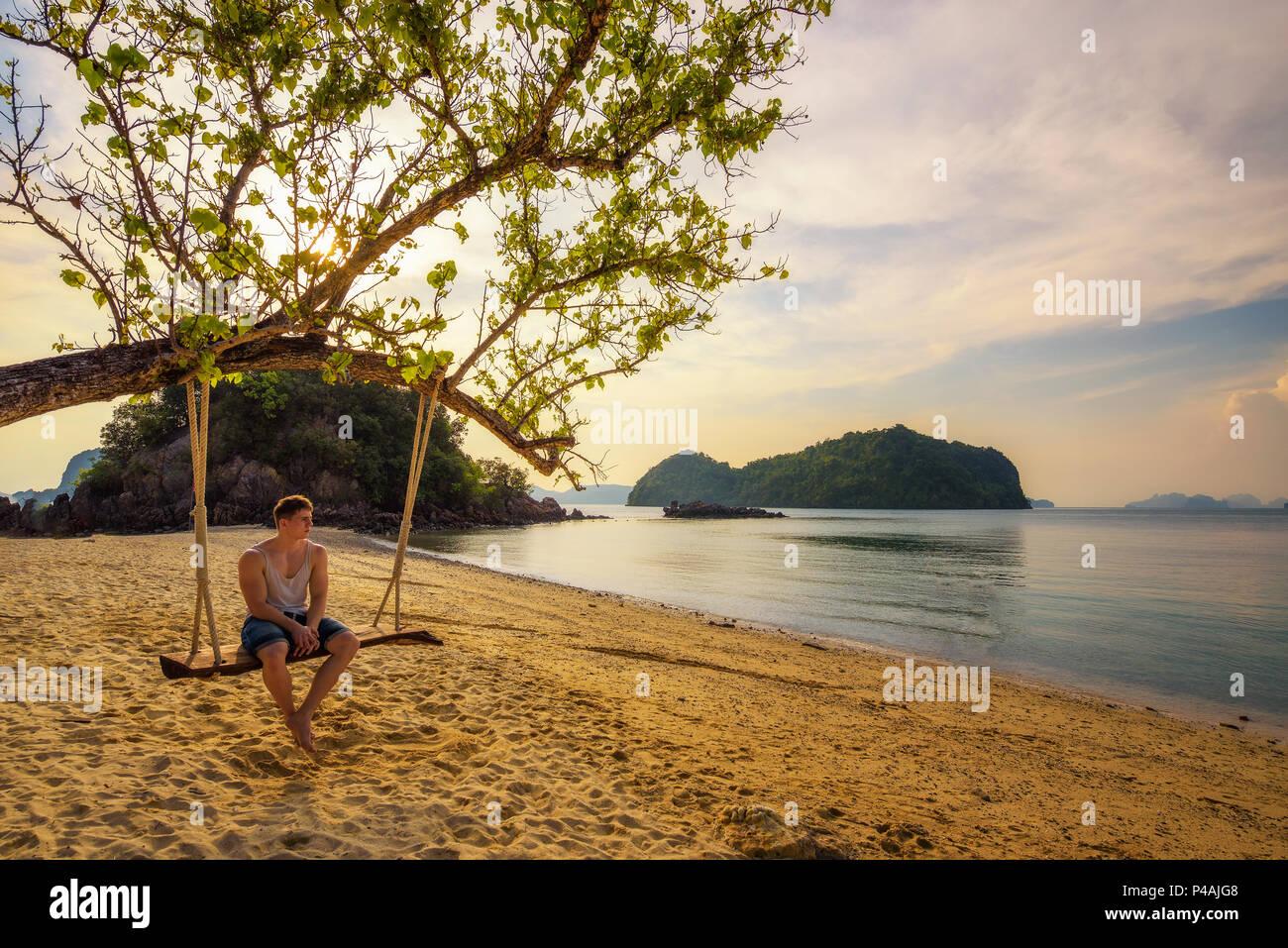 Ragazzo giovane gode di tramonto n Ko Hong Island in Thailandia Immagini Stock