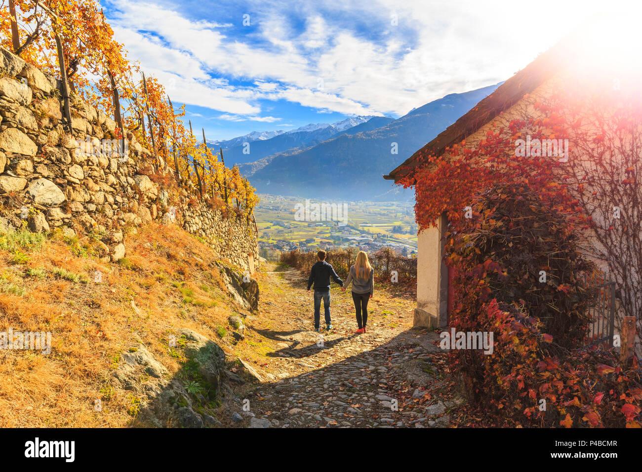 Due persone che camminano su di un sentiero tra i vigneti e una copertura della casa di uva americana foglie. A Poggiridenti, Valtellina, provincia di Sondrio, Lombardia, Italia. Immagini Stock