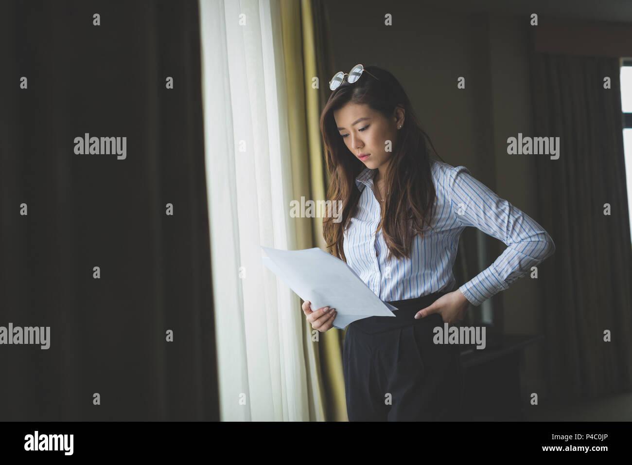 Imprenditrice la lettura del documento nella finestra vicino Immagini Stock