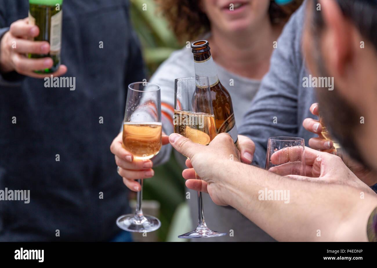 Gli amici la tostatura con bevande (lager e prosecco) in corrispondenza di un al di fuori di riunione sociale Immagini Stock