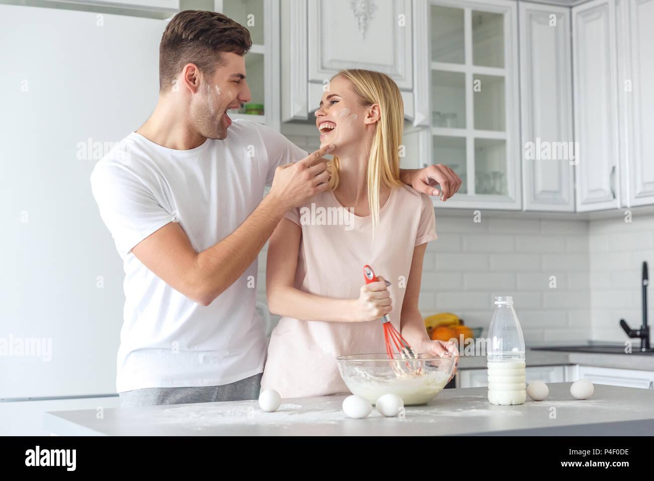 Amare giovane cooking per colazione insieme sulla cucina su weekend mattina Immagini Stock