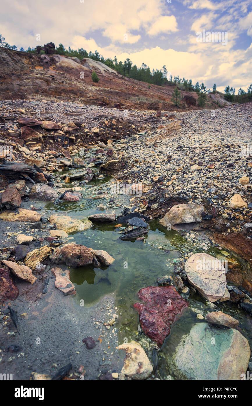 Verde acido acqua con PH basso giù per la montagna nella vecchia miniera Zaranda, Spagna Immagini Stock
