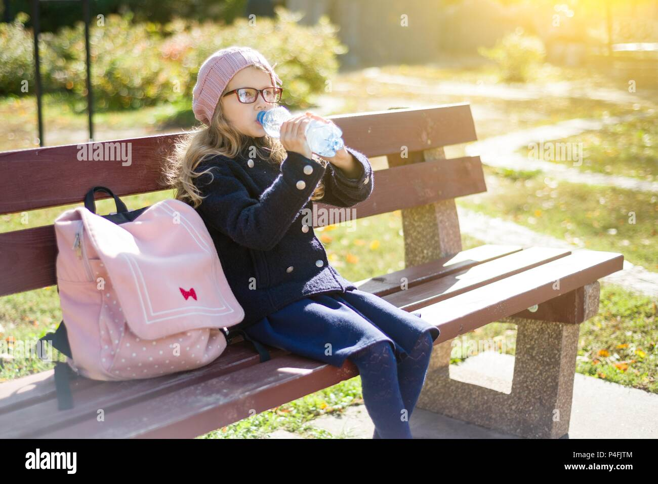 Bambina scuola elementare studente seduto sul banco di lavoro con