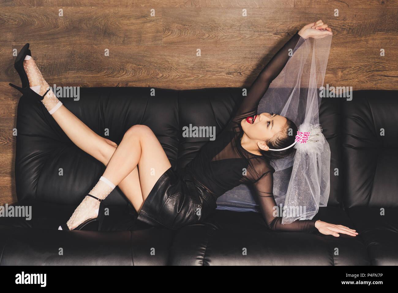 Felice fidanzato asiatici in velo sdraiato sul divano Immagini Stock