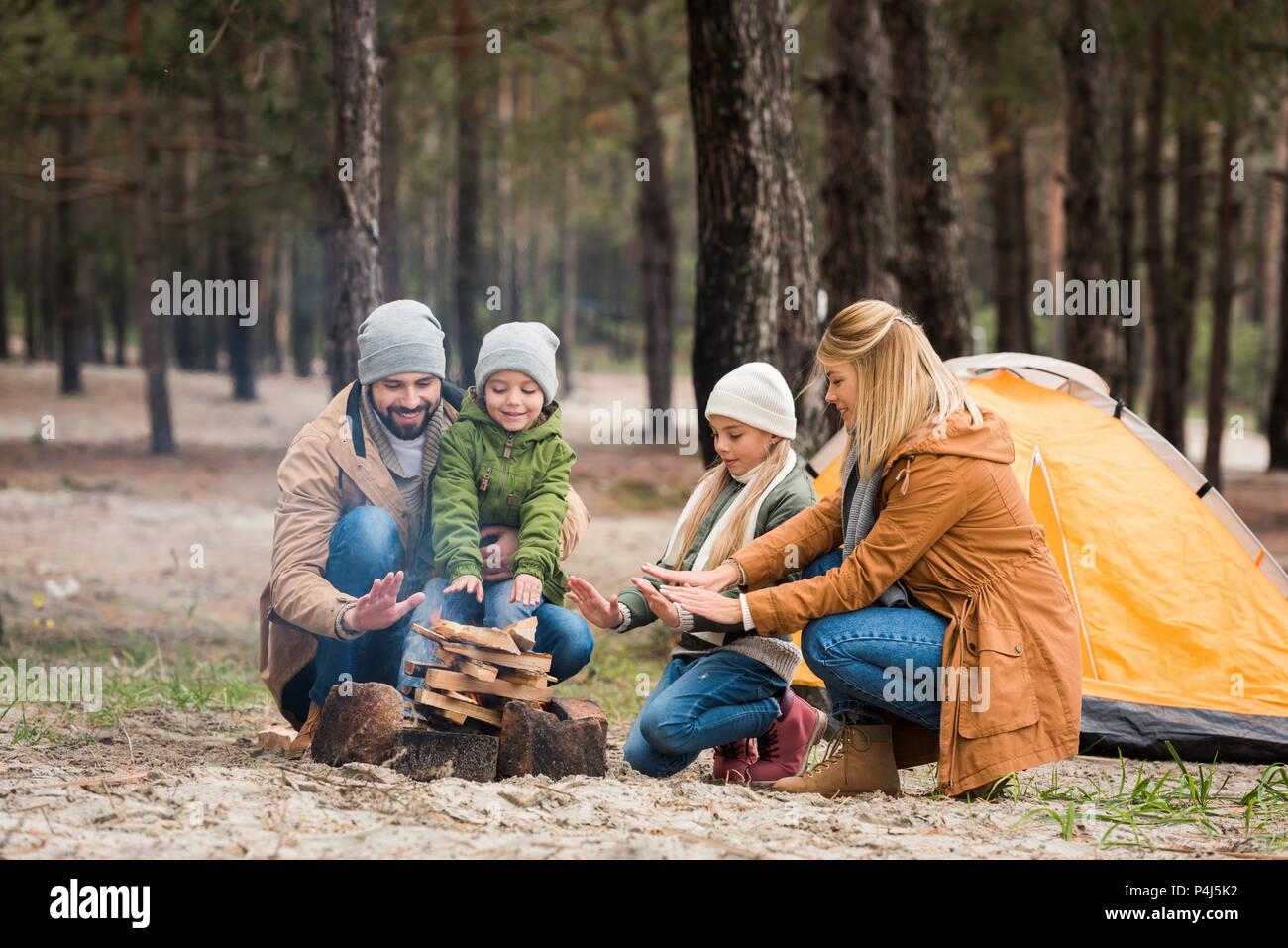 La famiglia felice riscaldando le mani con il falò pur avendo viaggio Immagini Stock