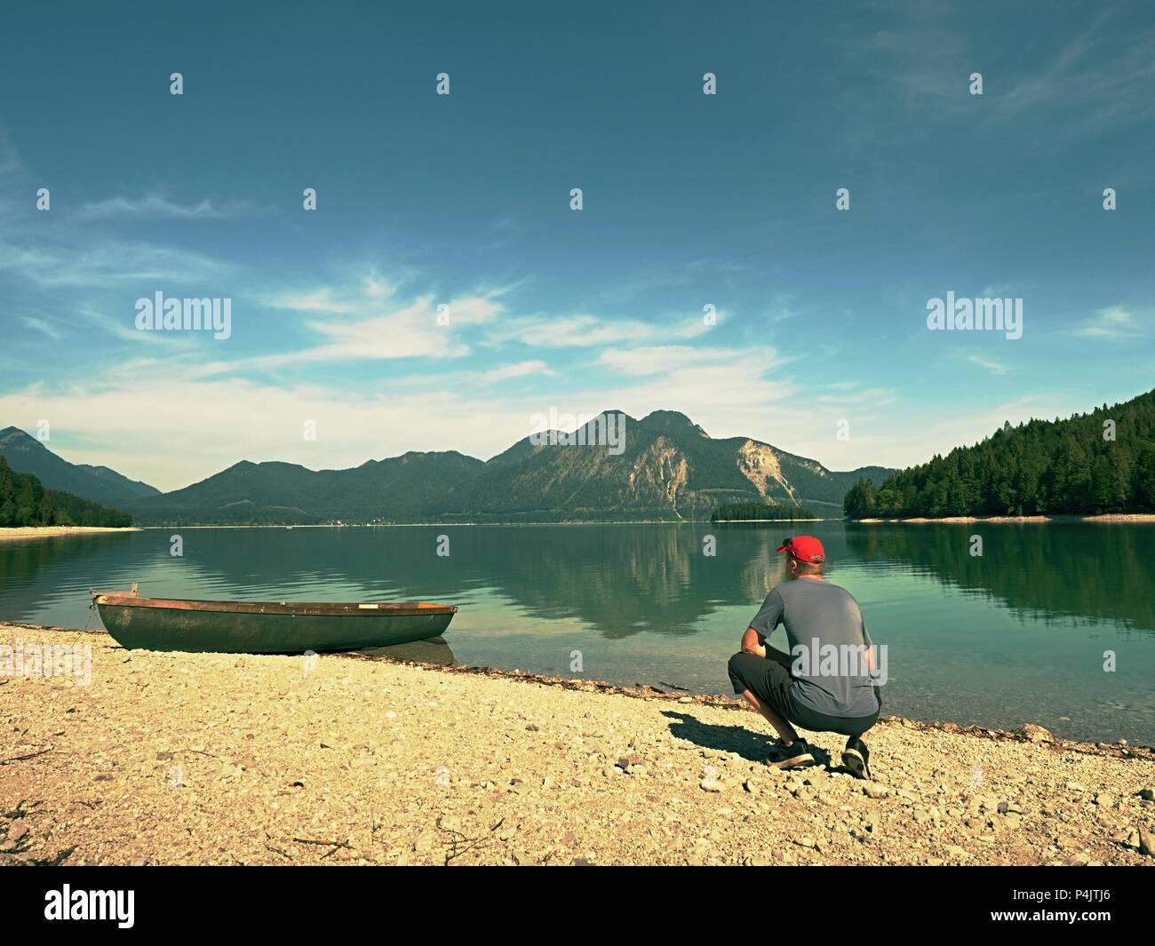 Uomo seduto sul sassoso banca di montagna alpina lago a ancorata laminato in barca. Immagini Stock