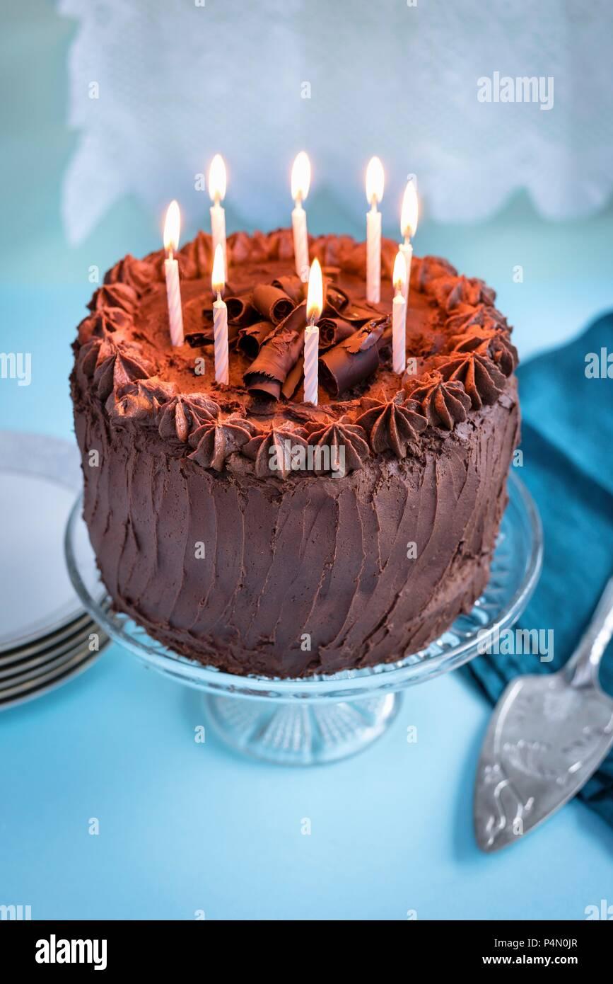 Cioccolato torta di compleanno con 8 candele accese sulla torta stand Immagini Stock