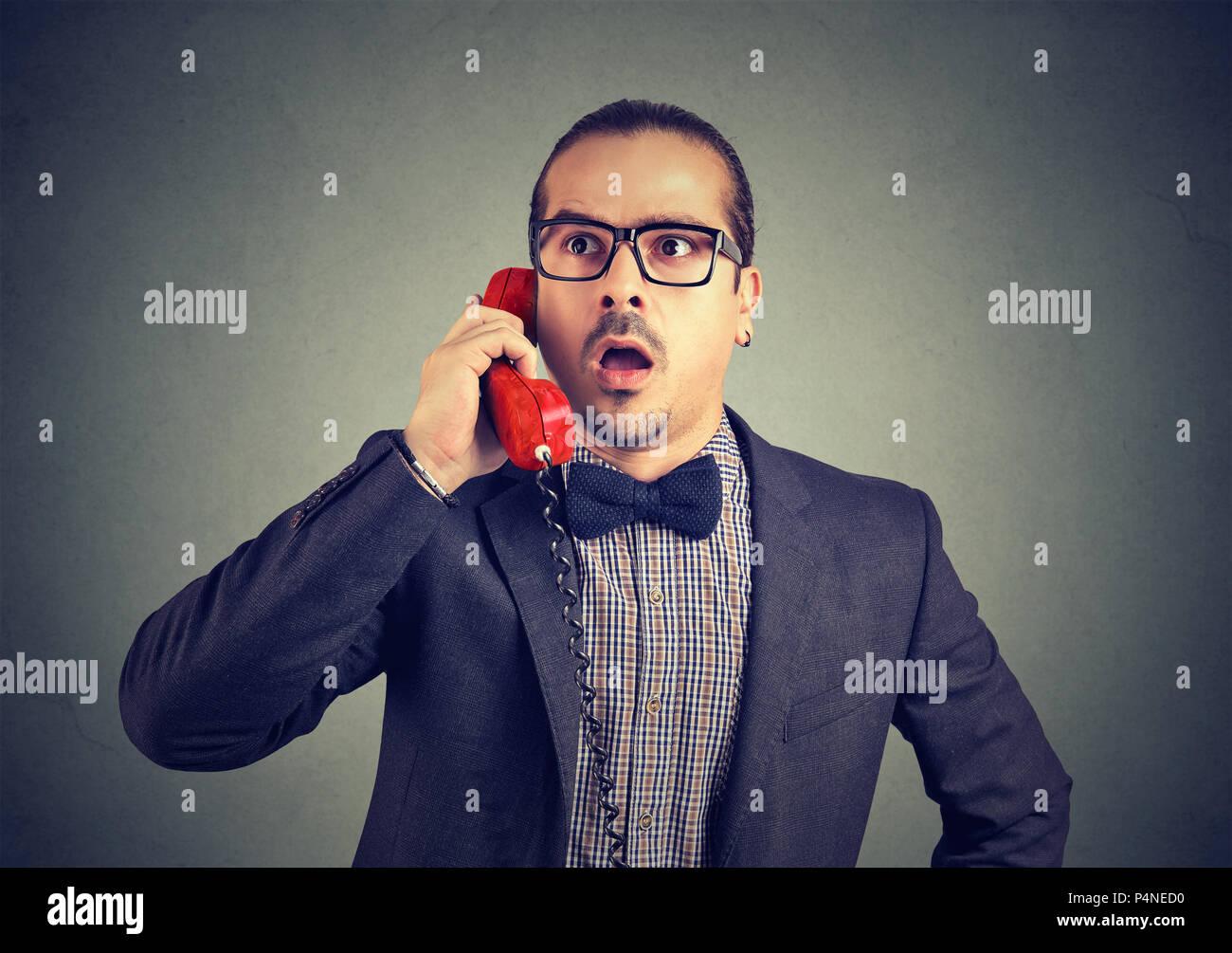 Elegante uomo stupito in bicchieri cerca storditi pur avendo chiamata sul telefono alla ricerca di distanza su sfondo grigio Immagini Stock