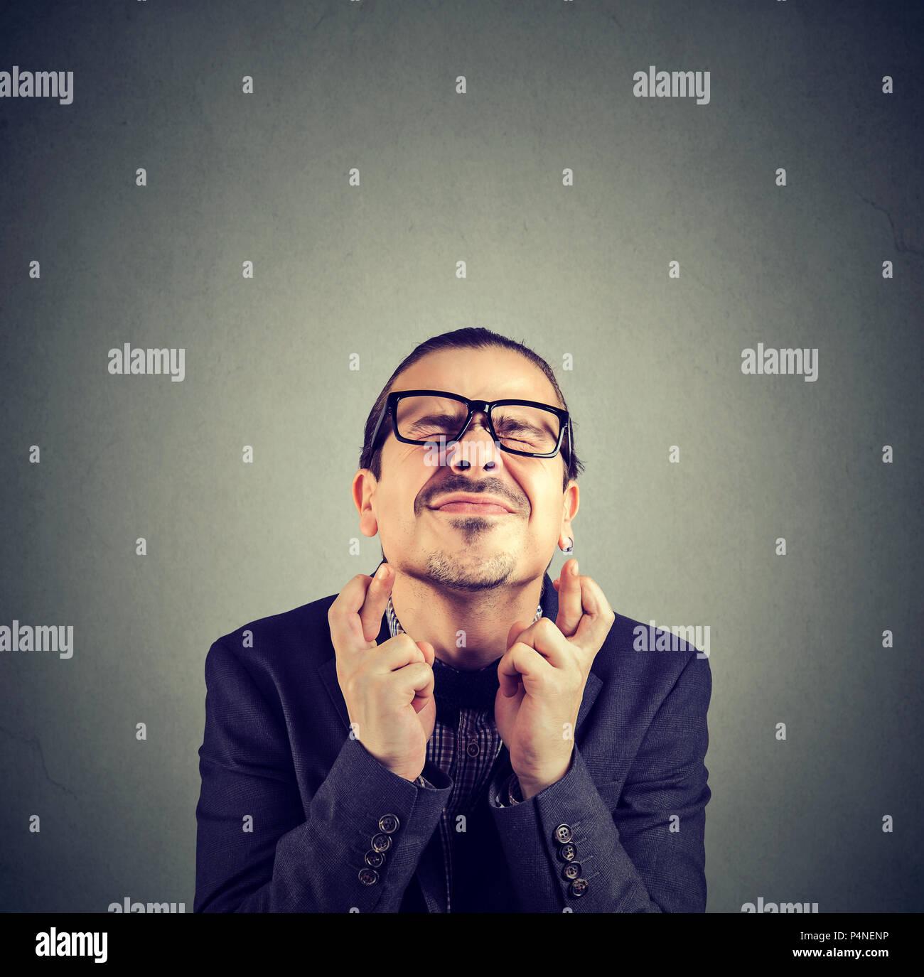 Giovani funny man in bicchieri tenendo le dita incrociate e gli occhi squinted rendendo nel contempo desidero su sfondo grigio Immagini Stock