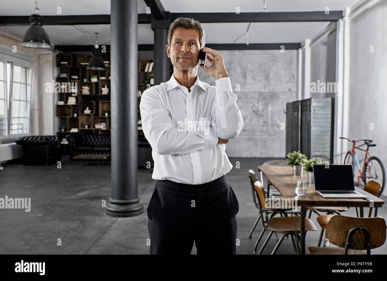 Ritratto di coppia uomo d affari utilizza lo smartphone in ufficio loft Immagini Stock