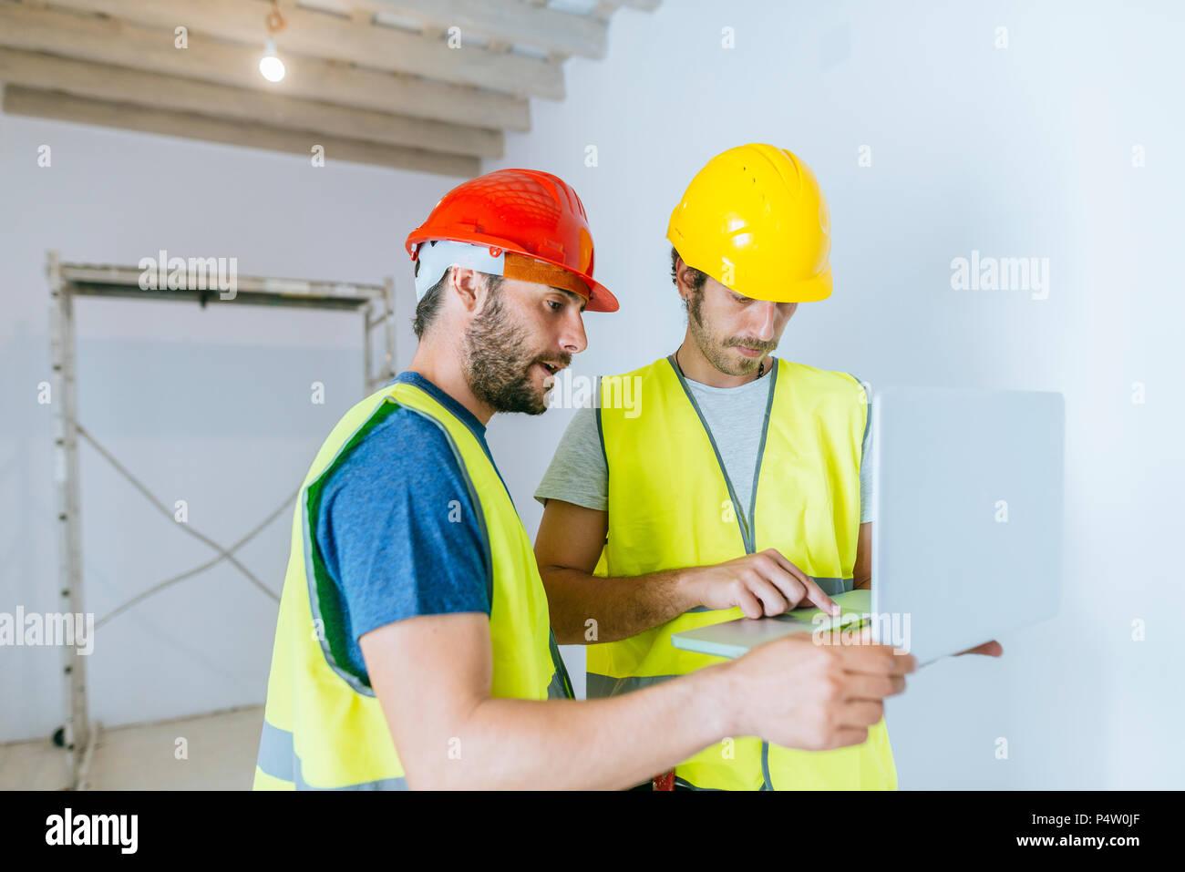 Lavoratori che utilizzano il portatile in sito in costruzione Immagini Stock
