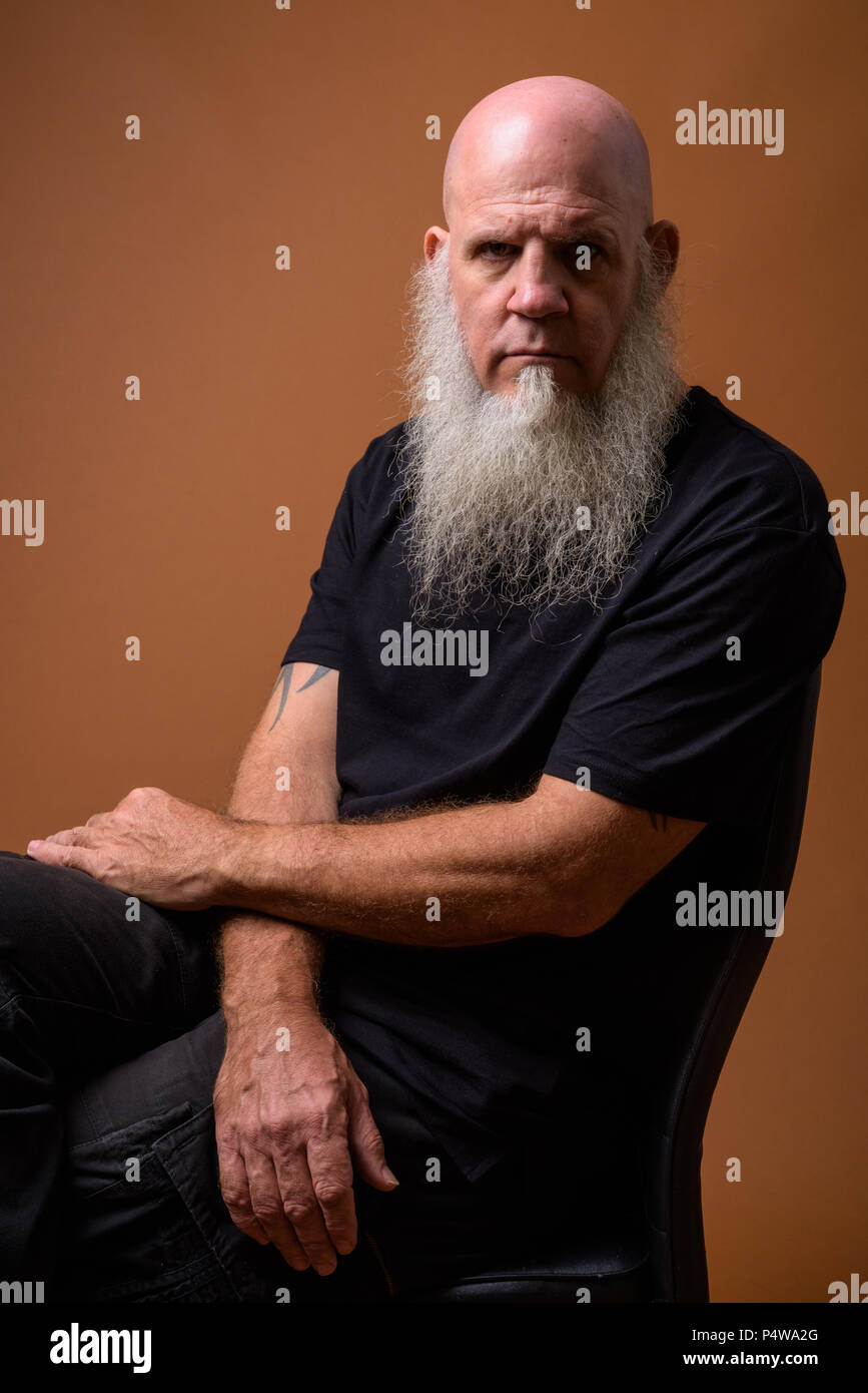 Coppia uomo calvo con una lunga barba grigia contro sfondo marrone Immagini Stock