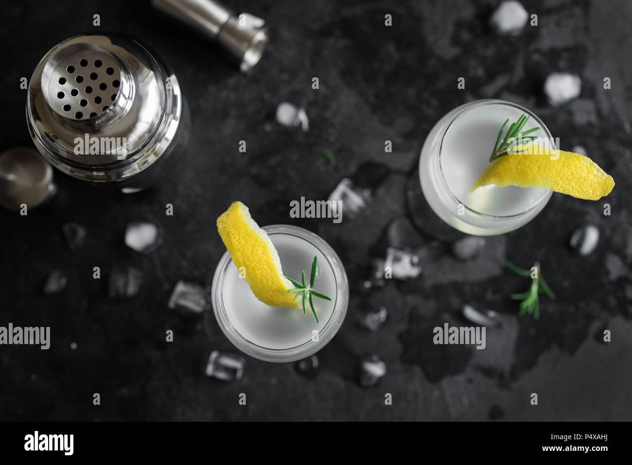 Cocktail alcolici con limone e rosmarino e ghiaccio. Il gin tonic fizz o succhiello cocktail su sfondo nero, copia dello spazio. Immagini Stock