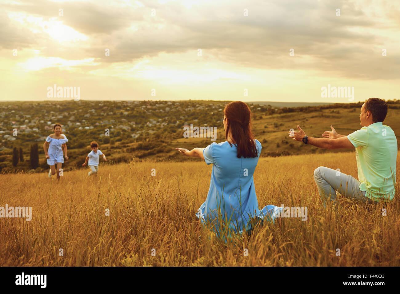 La famiglia felice giocando insieme all'esterno. Foto Stock