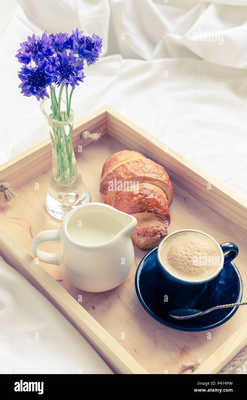 Romantico in estate la colazione a letto, vassoio con croissant freschi,  una tazza di caffè espresso con il latte e bouquet di cornflowers blu.