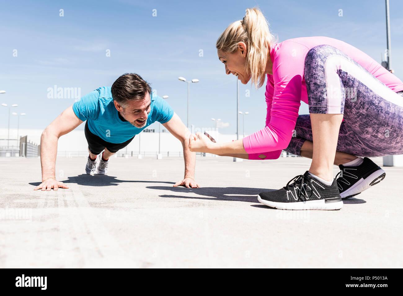 L'uomo exerfining pushups, donna lui di coaching Immagini Stock