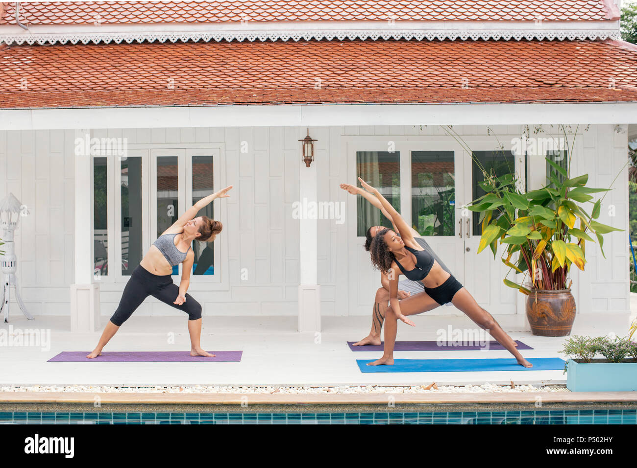 Due donne e un uomo a praticare yoga sulla terrazza Immagini Stock