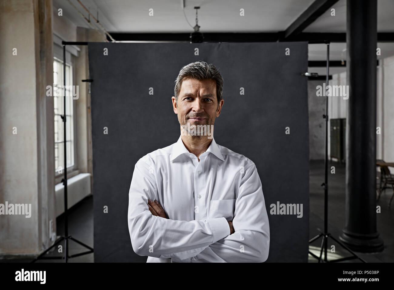 Ritratto di imprenditore maturo di fronte a sfondo nero in mansarda Immagini Stock