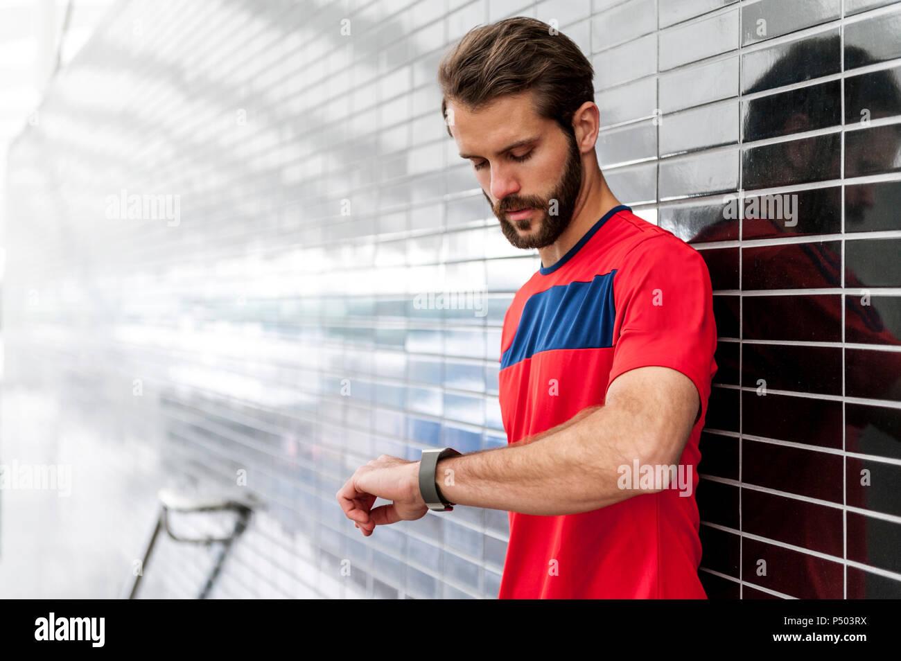 L'uomo avente una pausa dall'esecuzione controllando il tempo su un smartwatch Immagini Stock