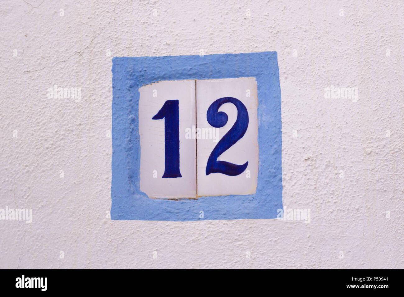 Numero di casa su piastrelle di ceramica sul muro bianco foto